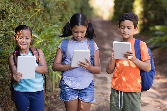 Boys and girls using digital tablets at natural parkland